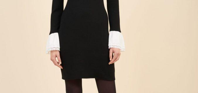 Modella posa in piedi con tubino nero e collant neri con tacchi