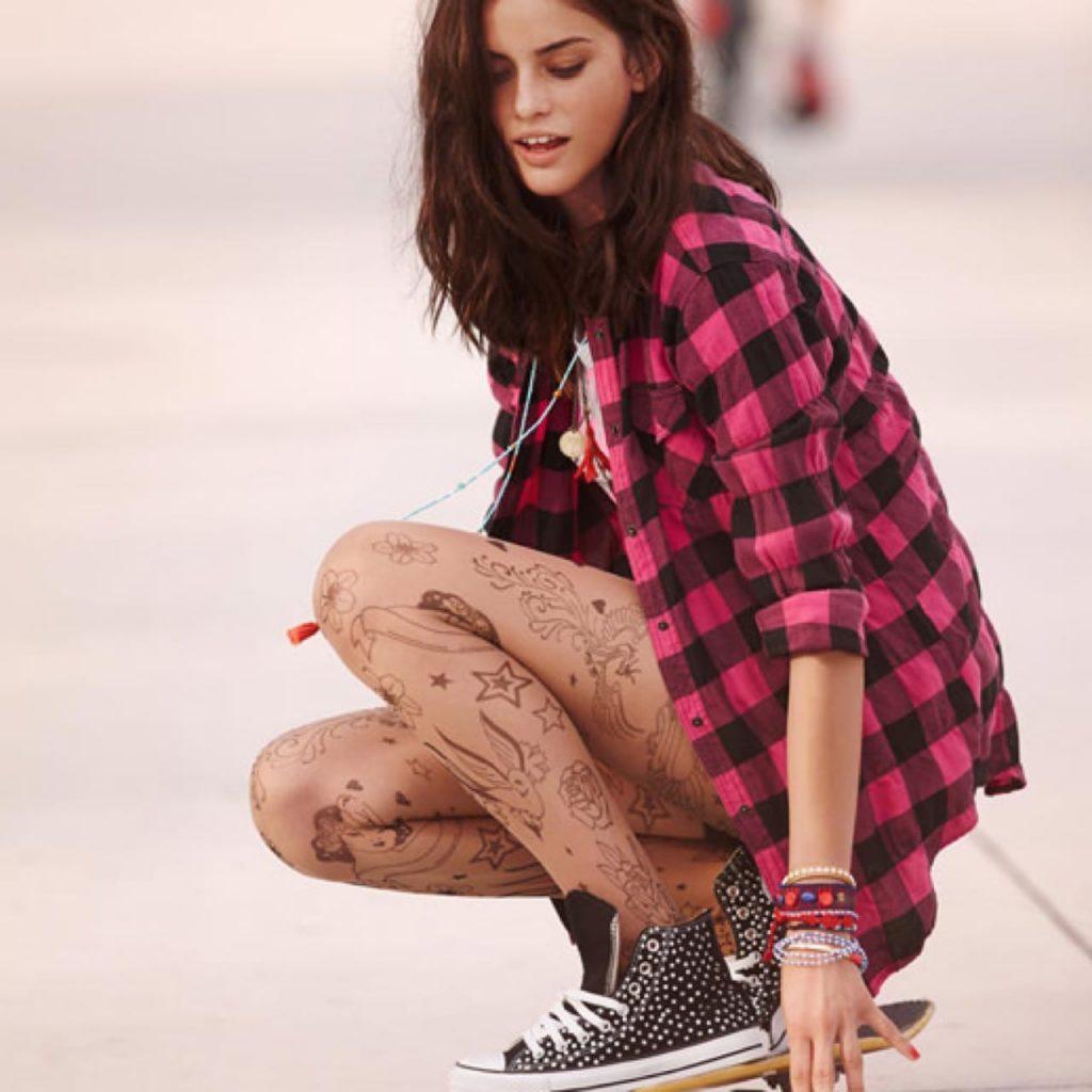 Ragazza sullo skateborad indossa calze con effetto tattoo